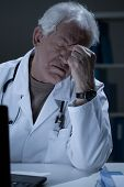 stock photo of sinuses  - Aged medic having sinus pain at work - JPG