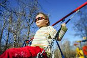 foto of seesaw  - Cute little girl swinging on seesaw on children playground - JPG