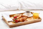 stock photo of bed breakfast  - breakfast in bed with coffee croissants strawberries and juice - JPG