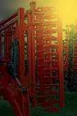 pic of cultivator-harrow  - Agricultural equipment in sunset light - JPG