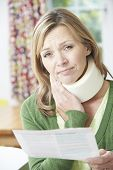 stock photo of neck brace  - Woman Reading Letter After Receiving Neck Injury