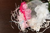 image of garter  - Beautiful pink roses pearl beads and garter lying on a table - JPG