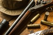 stock photo of cap gun  - Hunting rifle ammunition a knife and a cap on the wooden table close - JPG