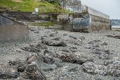stock photo of tide  - Low tide in West Seattle Washington reveals a rugged seabed leading up to a cement stariway that is built in to a seawall - JPG