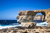 picture of gozo  - the rugged coastline of the island of Gozo are reflected in a blue sea - JPG