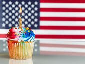picture of candle flame  - Close up of a red white and blue frosted cupcake with burning candle - JPG