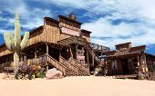 stock photo of wild west  - Old Wild West desert cowboy town with cactus and saloon - JPG