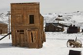 wild western leaning shack supported by a wood beam during an early snow fall in an old ghost town