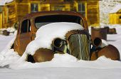 old pre-wwii rusted car burried in snow