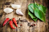 picture of bay leaf  - fresh bay leaves garlic cloves red chili pepper on a rustic wooden background - JPG