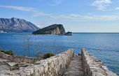 pic of sea-scape  - The view over Saint Nikolas island and the Adriatic sea from the top of the ancient citadel in the old town center of Budva the path seems to lead directly into the sea - JPG