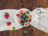 picture of porridge  - A bowl of oat porridge with fresh berries honey almond petals and leaves of mint over a piece beige linen fabric on a dark wooden background - JPG