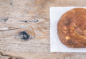 stock photo of home-made bread  - A half of home made village potato bread over a rough old wood surface - JPG