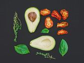 foto of avocado  - Avocado dried tomatoes green basil leaves and thyme on a black paper surface - JPG