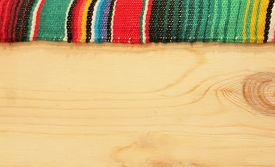 picture of mexican fiesta  - fiesta mexican poncho rug in bright colors with wood background with copy space - JPG