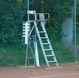 picture of umpire  - Old tennis umpire chair on a red tennis court - JPG