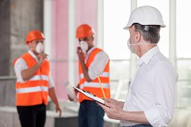 stock photo of respirator  - Experienced old architect is discussing with builders the concepts of building - JPG
