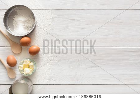 poster of Baking background with copy space. Cooking ingredients for yeast dough and pastry, eggs, flour and milk on white rustic wood. Mockup for menu, recipe or culinary classes.