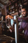 Bar tender filling beer from bar pump at bar counter poster