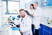 Portrait Of Young Handsome Bearded Stylish Intern, Who Is Wearing Gloves And Labcoat, Safety Glasses poster