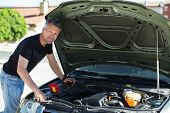 Oil change in car. Man repairing the engine in the car. Self-changing oil in own car. Man looks unde poster