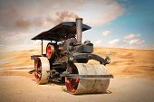 Old steam roller on riding on desert after apocalypse. Steam engine from 19th century on retro style poster