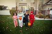 Group of kids dressed in Halloween costumes going trick or treating outdoors in October in a residen poster