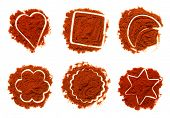 piles of ground paprika chilies on white, six different shapes, bright red color, sharp shot.