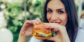 Happy Young Woman Eat Tasty Fast Food Burger poster