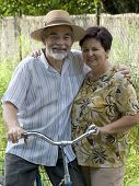 stock photo of senior-citizen  - An attractive senior couple with bicycle outdoors - JPG