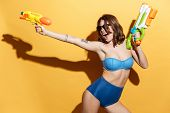 Photo of happy screaming woman in swimwear isolated over yellow background holding toys water gun. L poster