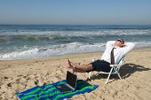 stock photo of business success  - A businessman takes his office to the beach - JPG