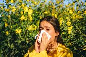 Sneezing Young Girl With Nose Wiper Among Blooming Flowers In Park. Young Woman Got Nose Allergy, Fl poster
