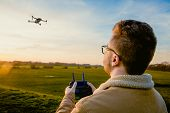 A Male Drone Pilot With A Pilot Licence Using A Remote Control To Fly A Quadcopter Style Drone For P poster
