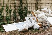 Construction Garbage After Apartment Repair. Pile Of Construction Waste Near A White Brick Wall. Con poster