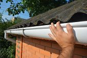House Asbestos Roof With Plastic Roof Gutter Pipe Repair. Contractor Hand Repair House Roof Gutter. poster