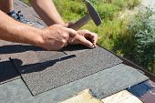 Roofing Contractor Installing Roof Tiles, Asphalt Shingles With Hammer And Nails. Roofing Constructi poster