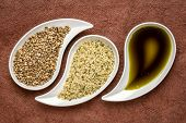 dry hemp seeds, hearts and oil in small teardrop bowls against brown textured bark paper poster
