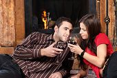 Couple Near Fireplace Holding Glass Of Wine