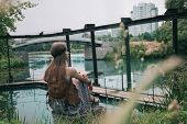 Young Hippie Woman Sitting Near A City Pond poster