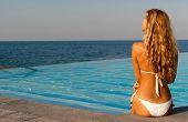 Beautiful Woman In White Bikini Sitting Near Infinity Pool