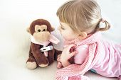 Baby In A Warm Pink Scarf With Monkey. Childrens Toy With Medical Thermometer. Thermometer Medical D poster