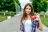 Girl Schoolgirl Teenager 10-15 Years. In His Hand A Toy Heart. Happy Smiling In A City Summer Park.  poster