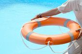 Hands Of The Rescuer With Lifebuoy In Pool. Hotel Worker Throws A Lifeline To A Drowning Pool. Salva poster