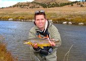 foto of brook trout  - Man holding a brown trout caught fly fishing on a meandering meadow stream - JPG