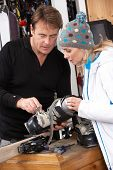 pic of ski boots  - Sales Assistant Helping Advising Female Customer On Ski Boots In Hire Shop - JPG