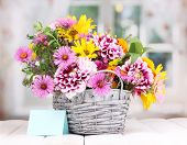image of wooden basket  - beautiful bouquet of bright flowers in basket on wooden table - JPG