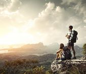 stock photo of mountain-high  - Hikers with backpacks enjoying valley view from top of a mountain - JPG