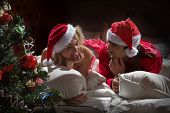 Young couple in Santa's hats  in white bed