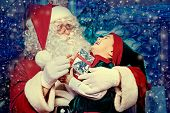 image of elf  - Santa Claus sitting with a little cute boy elf over Christmas background - JPG